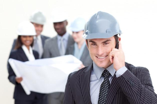 Arquiteto masculino confiante com sua equipe no fundo Foto Premium
