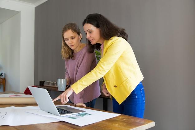 Arquiteto sério que mostra o projeto da casa na tela do laptop Foto gratuita