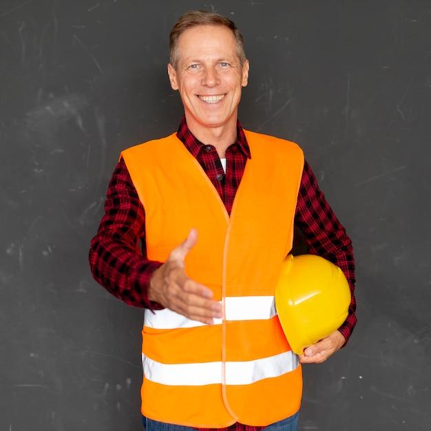 Arquiteto sorridente dando um aperto de mão Foto gratuita