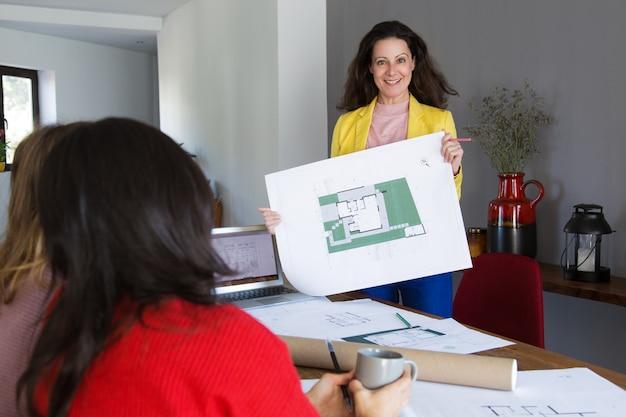 Arquiteto sorridente, mostrando o projeto da casa para clientes ou colegas Foto gratuita