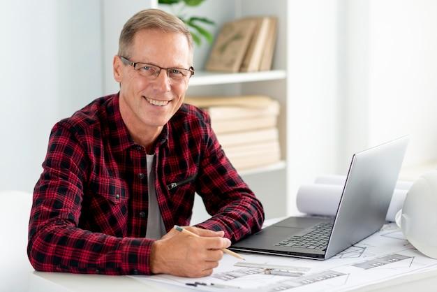 Arquiteto sorridente usando óculos e olhando para a câmera Foto gratuita