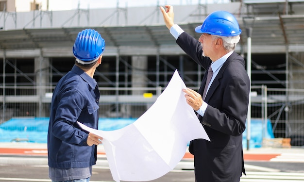 Arquitetos desenvolvedores revisando planos de construção no canteiro de obras Foto Premium