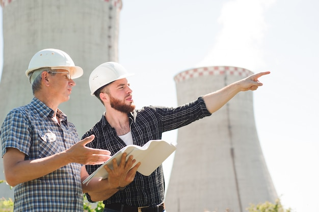 Arquitetos masculinos revisando documentos juntos em energia elétrica Foto Premium