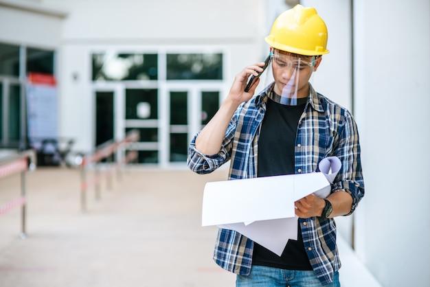 Arquitetos seguram plantas e falam ao telefone. Foto gratuita