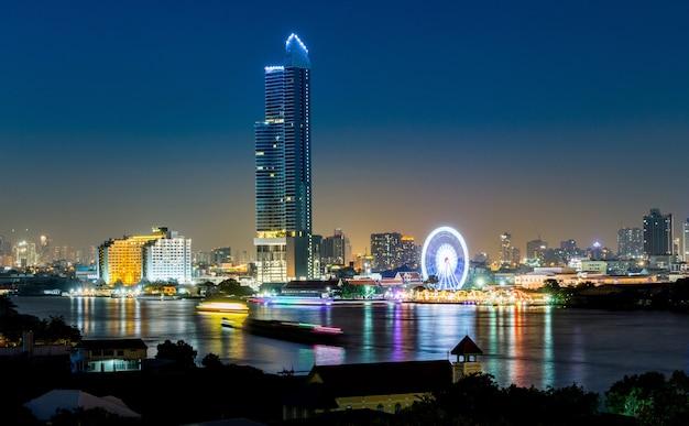 Arquitetura de noite edifício de escritórios de negócios e roda gigante em bangkok Foto Premium
