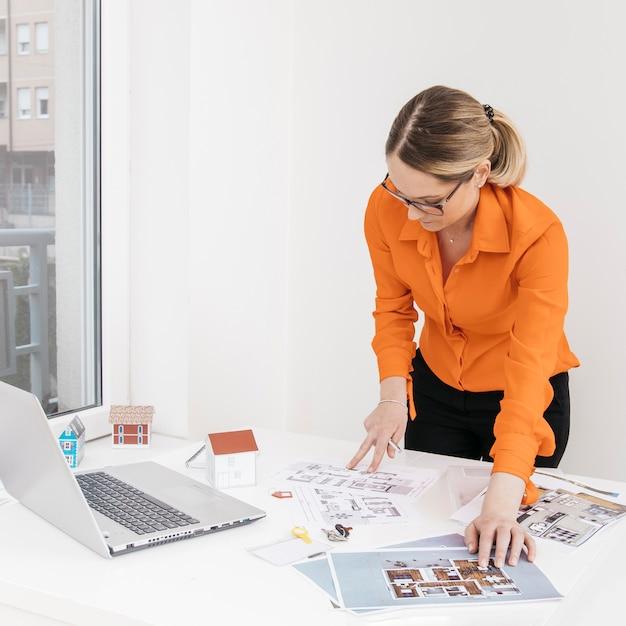 Arquitetura feminina, inspecionando, blueprint, escrivaninha, em, escritório Foto gratuita