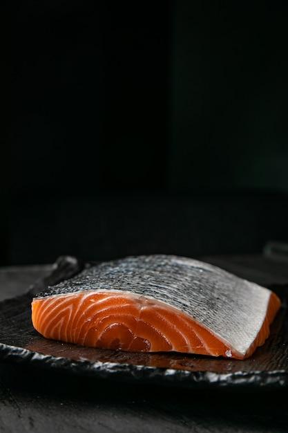 Arquivo de salmão cru no quadro cinza e superfície preta Foto Premium