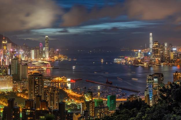 Arranha-céu de hong kong cityscape na hora do crepúsculo, hong kong central e ilha de kowloon, victoria pico e porto, aventura e trekking no ponto de vista do cume vermelho queimador de incenso para viajantes Foto Premium
