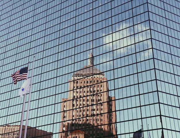 Arranha-céu de vidro construindo com a bandeira americana e reflexão de prédio alto Foto gratuita