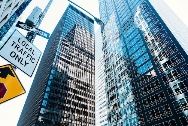 Arranha-céus altos de vidro e sinal de trânsito na rua Foto gratuita