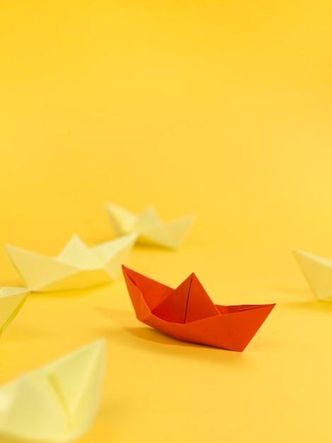 Arranjo abstrato com barquinhos de papel no espaço amarelo de fundo e cópia Foto Premium