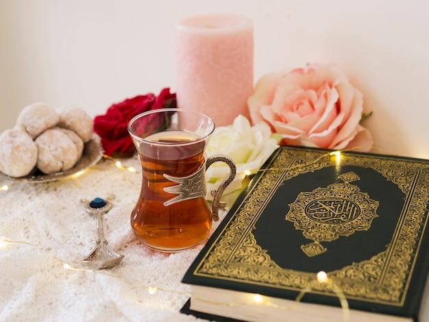 Arranjo com alcorão, rosas, velas, chá e biscoitos Foto gratuita