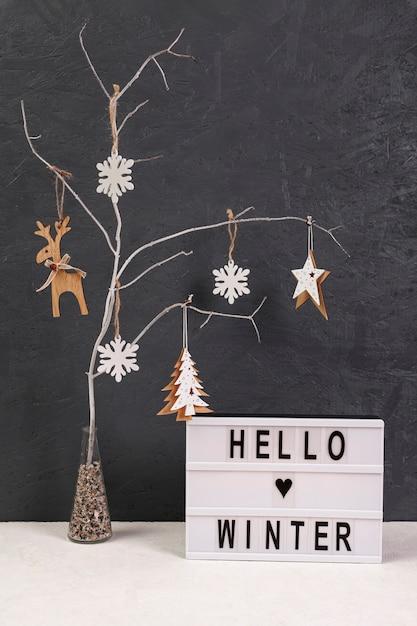 Arranjo com árvore e olá sinal de inverno Foto gratuita