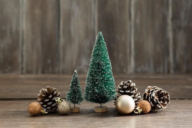Arranjo com árvores de natal e pinhas Foto gratuita