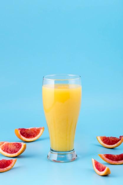 Arranjo com copo de suco de laranja Foto gratuita