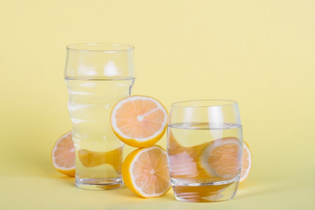 Arranjo com copos de água e limões Foto gratuita
