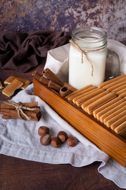 Arranjo de alto ângulo com leite em uma jarra e biscoitos Foto gratuita