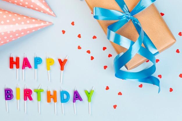 Arranjo de aniversário plano com chapéu de presente e festa Foto gratuita