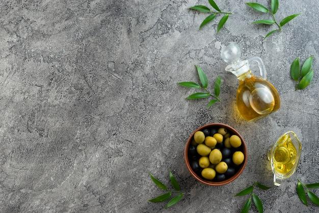 Arranjo de azeitonas e óleos em fundo de mármore Foto gratuita