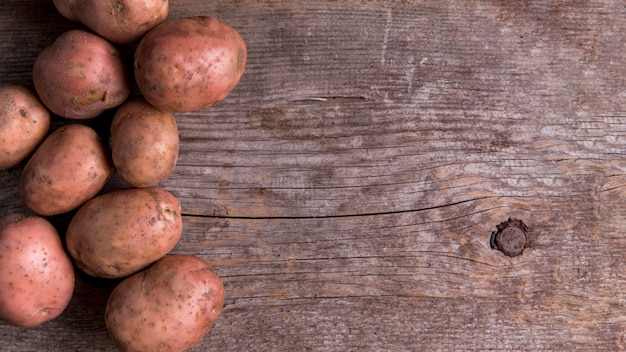 Arranjo de batatas em fundo de madeira com espaço de cópia Foto Premium