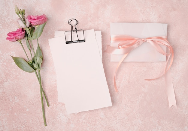 Arranjo de casamento liso leigos com convite e flores Foto gratuita