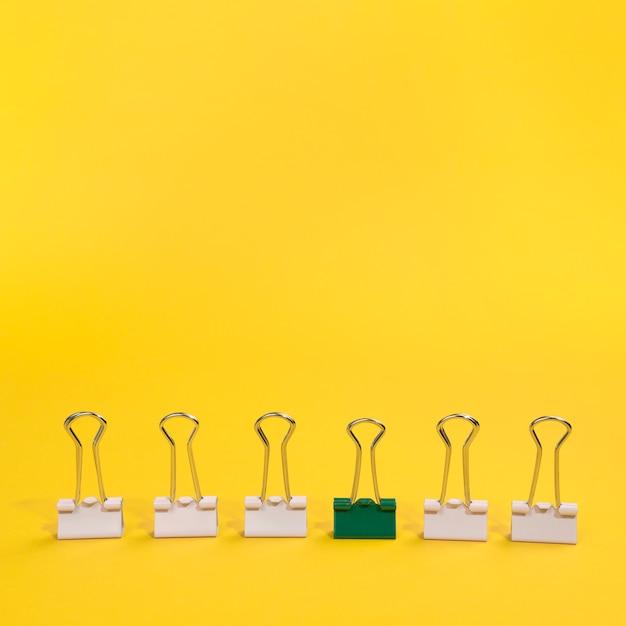 Arranjo de clipes de papel com um clipe de papel verde Foto gratuita