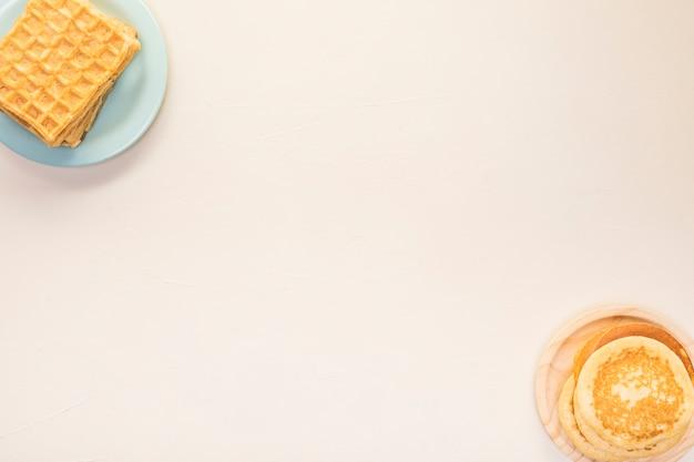 Arranjo de comida plana leigos com panquecas e waffles Foto gratuita