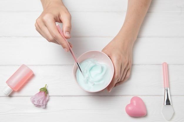 Arranjo de cosméticos plana leigos mãos sobre fundo branco de madeira Foto gratuita