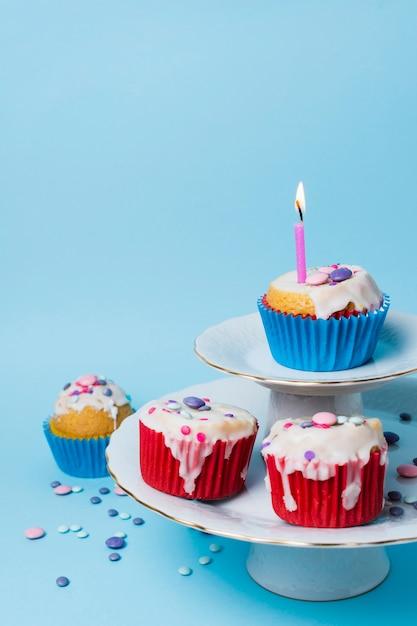 Arranjo de cupcakes de aniversário em fundo azul Foto gratuita