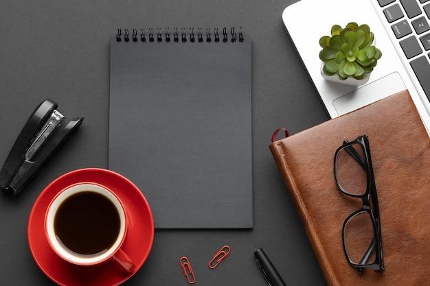 Arranjo de elementos de escritório em fundo escuro com bloco de notas Foto gratuita