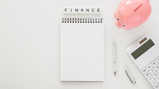 Arranjo de elementos financeiros com bloco de notas vazio Foto gratuita
