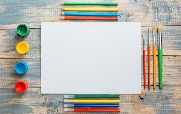 Arranjo de equipamentos de pintura colorida e folha em branco sobre fundo de madeira Foto gratuita