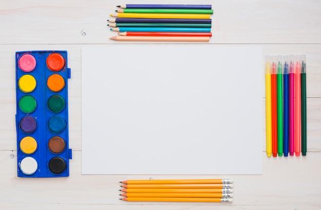 Arranjo de equipamentos de pintura e papel branco na mesa Foto gratuita