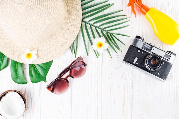 Arranjo de férias tropicais com protetor solar, câmera, cabana, óculos de sol, coco, flores e folhas de palmeira Foto gratuita