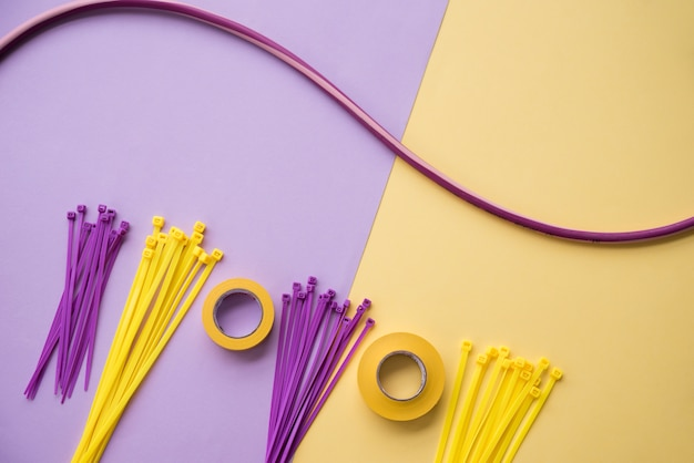 Arranjo de fita isolante e nylon zip fio sobre pano de fundo duplo roxo e amarelo Foto gratuita