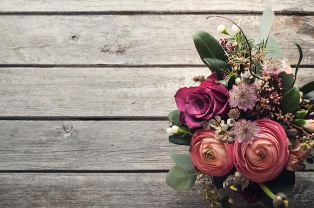 Arranjo de flores de rosas e ranúnculo em fundo de madeira Foto Premium