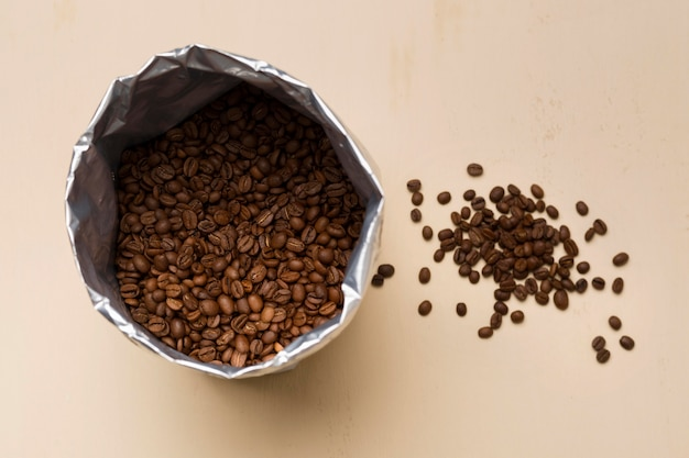 Arranjo de grãos de café preto sobre fundo bege Foto gratuita