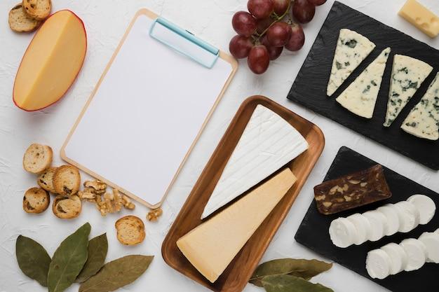 Arranjo de ingrediente de pequeno-almoço saudável com prancheta em branco vazia no fundo branco Foto gratuita
