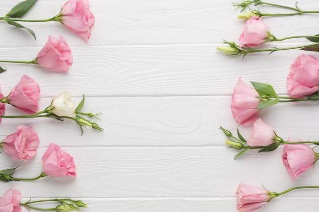 Arranjo de leigos plana com rosas rosa em fundo de madeira Foto gratuita
