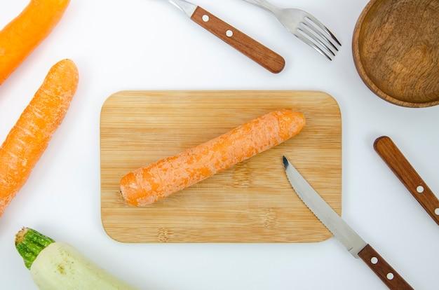 Arranjo de leigos plano com cenoura na placa de corte Foto gratuita