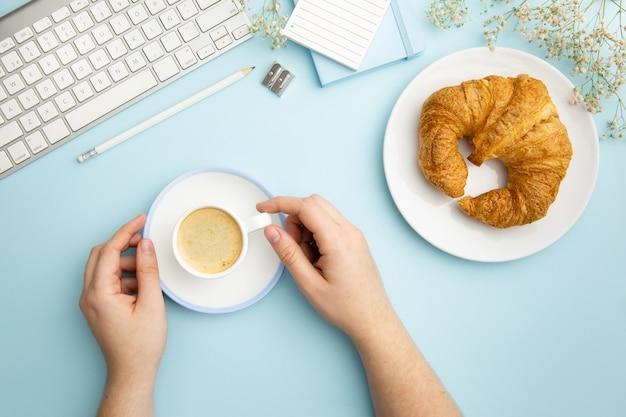 Arranjo de local de trabalho liso leigos sobre fundo azul com café da manhã Foto gratuita