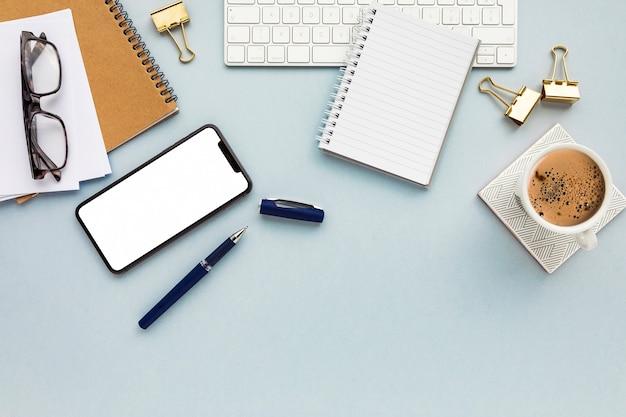 Arranjo de negócios minimalista sobre fundo azul, com espaço de cópia Foto gratuita