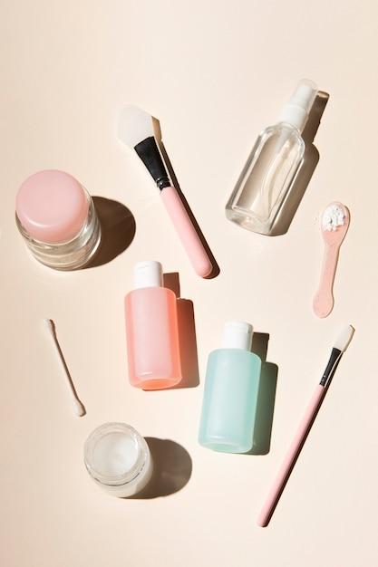 Arranjo de produtos de cuidado de corpo em fundo rosa de poeira Foto gratuita