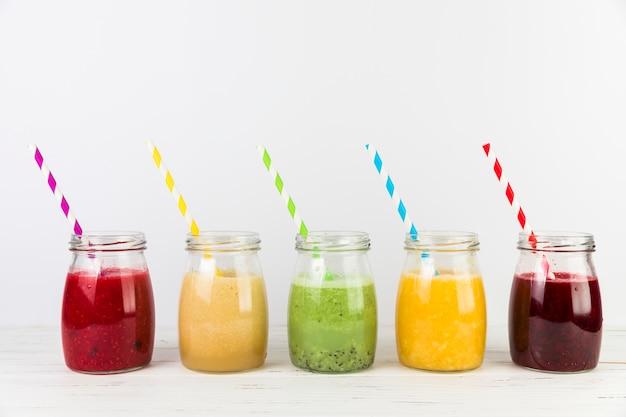 Arranjo de smoothies com canudos Foto gratuita