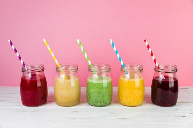 Arranjo de smoothies com fundo rosa Foto gratuita