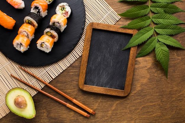 Arranjo de sushi plana leigos com quadro preto Foto gratuita
