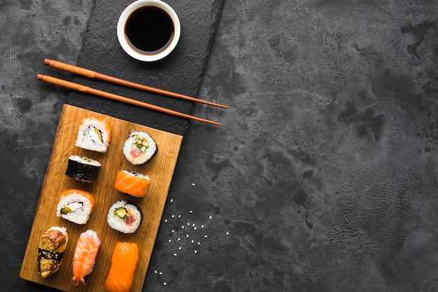 Arranjo de sushi plana leigos em fundo de ardósia Foto gratuita