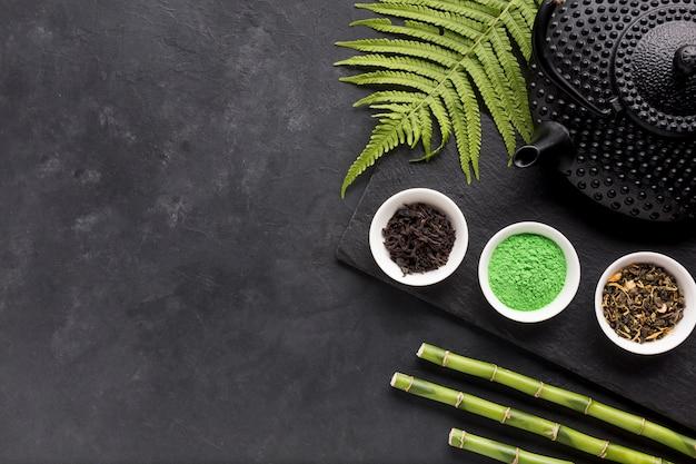 Arranjo de tigela pequena de chá de ervas com folhas de samambaia e vara de bambu Foto gratuita