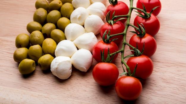 Arranjo de tomates vermelhos alegres; queijo; azeitonas sobre a superfície de madeira Foto gratuita
