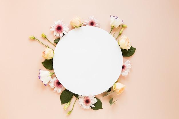 Arranjo de várias flores da primavera e pedaço de papel redondo vazio Foto gratuita